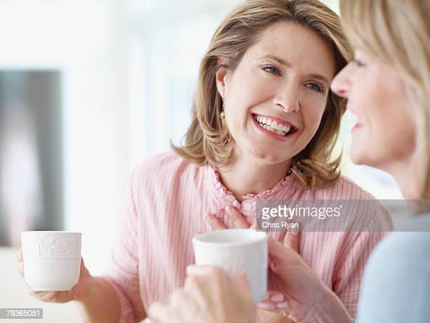 Two women indoors holding mugs and talking