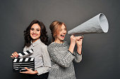 two women inform about the beginning of shooting. With speakerphone and clapperboard.