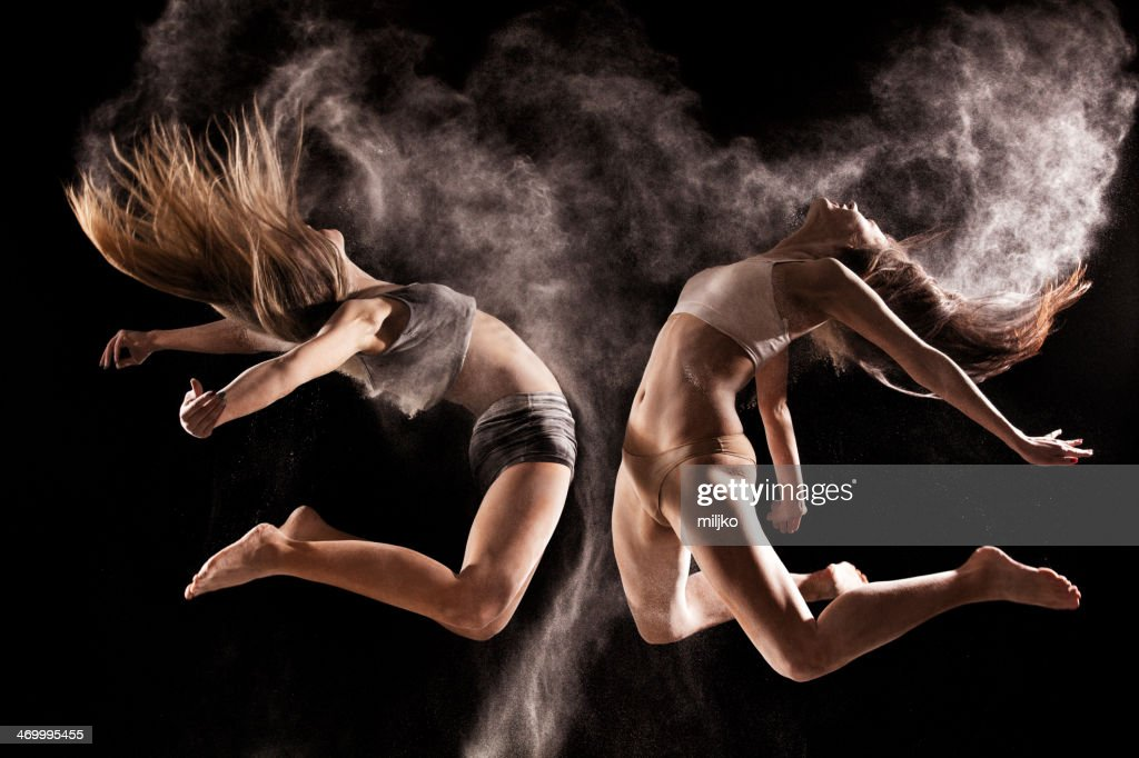 Two women jumping in a cloud of  powder