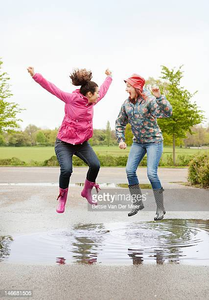 Two women jumping in puddle.