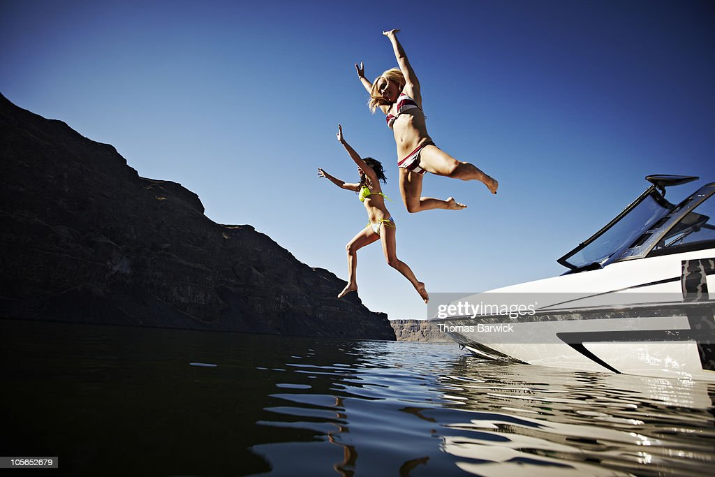 Two women jumping off ski boat into river