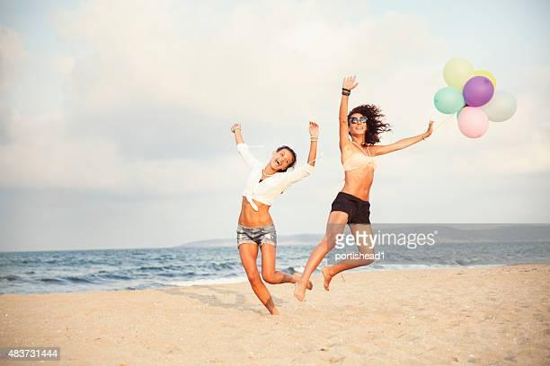 Zwei Frauen springen am Strand