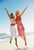 Two women jumping on the beach
