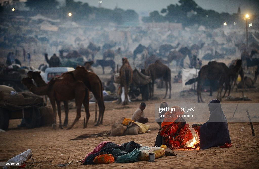 Two women keep warm by a fire at dawn at the camel fair grounds in the outskirts of Pushkar on November 21, 2012. The annual five-day camel and livestock fair, held in the town of Pushkar in the state of Rajasthan is one of the world's largest camel fairs, and apart from buying and selling of livestock it has become an important tourist attraction. AFP PHOTO/Roberto Schmidt