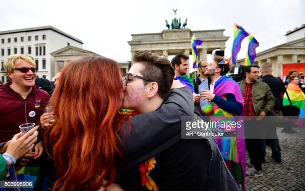 Two women kiss as they attend a rally of gays and lesbians in front of the Brandenburg Gate in Berlin on June 30 2017 The German parliament legalised...