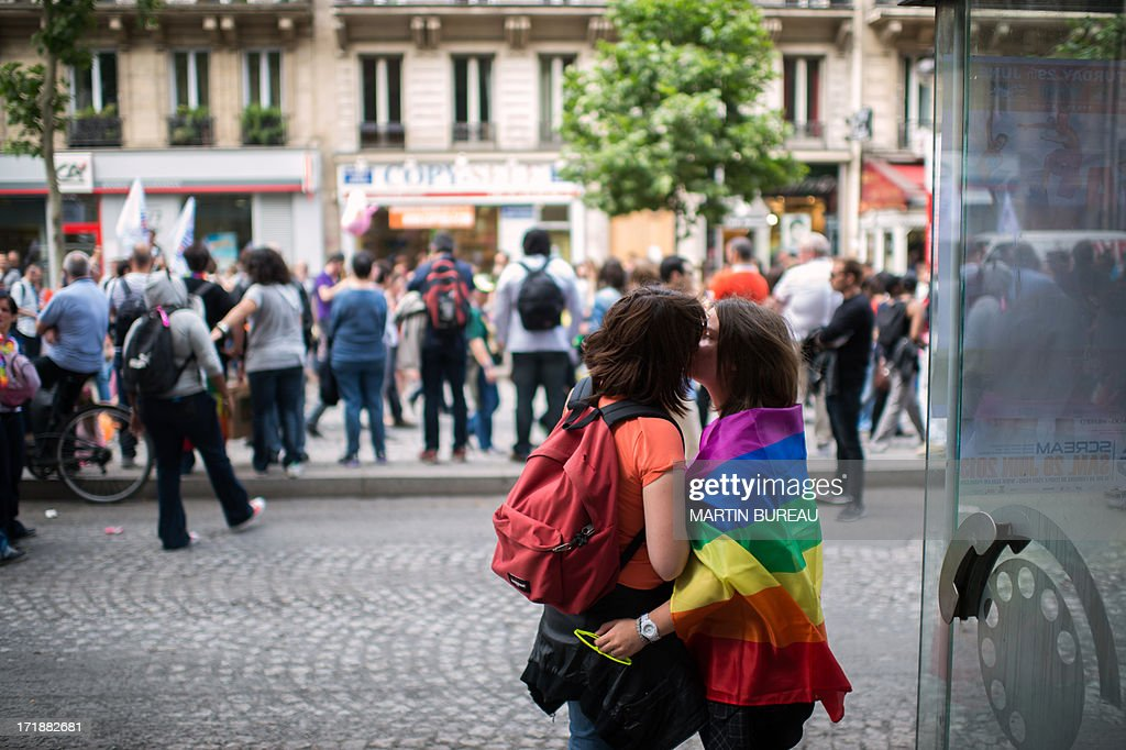 Two women kiss each other during the homosexual, lesbian, bisexual and transgender (HLBT) visibility march, the Gay Pride, on June 29, 2013 in Paris, exactly one month to the day since France celebrated its first gay marriage. AFP PHOTO / MARTIN BUREAU