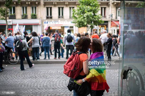 Two women kiss each other during the homosexual lesbian bisexual and transgender visibility march the Gay Pride on June 29 2013 in Paris exactly one...