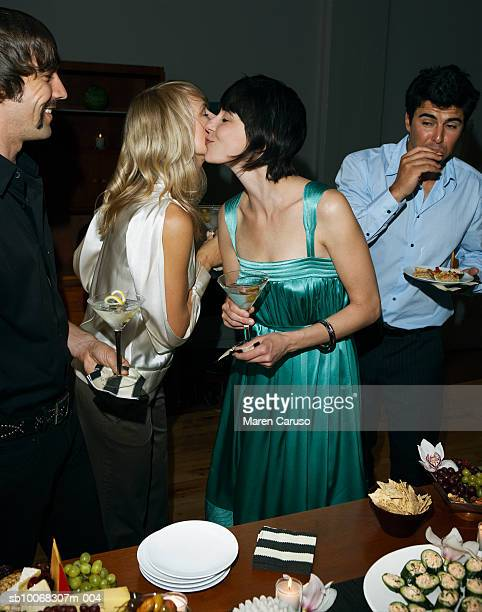 Two women kissing beside table at cocktail party