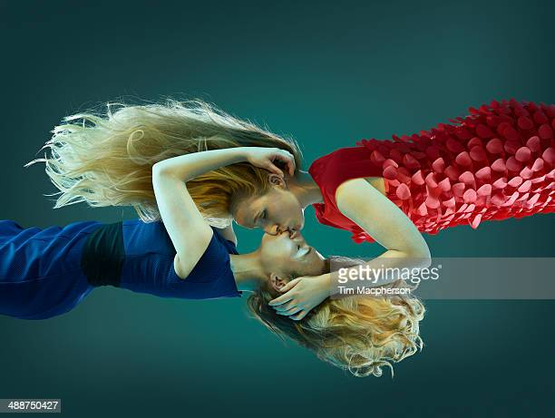 Two women kissing, floating in mid air