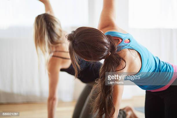 Two women kneeling and raising arms in pilates class