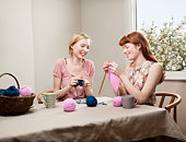two women knitting at table.