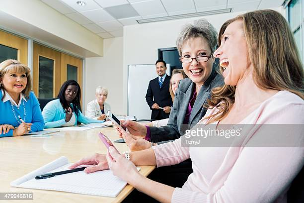 Two Women Laugh at Cell Phone Images at Business Meeting