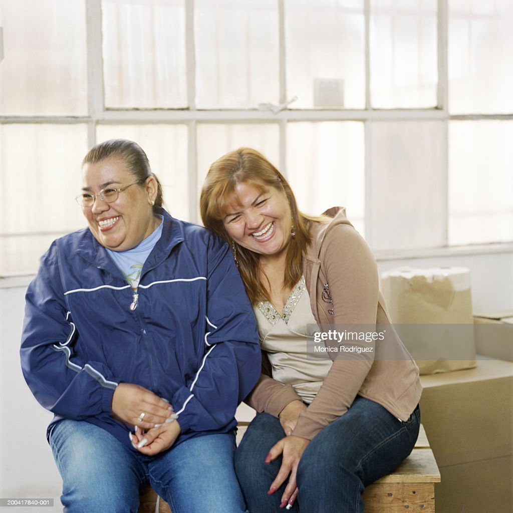 Two women laughing in garment factory : Stock Photo