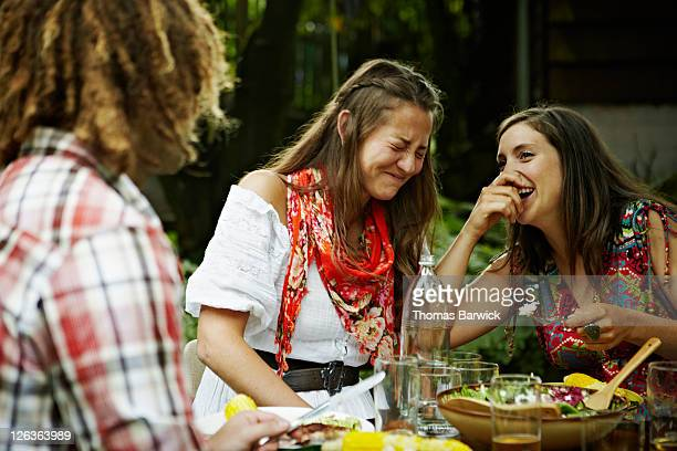 Two women laughing together at dining table