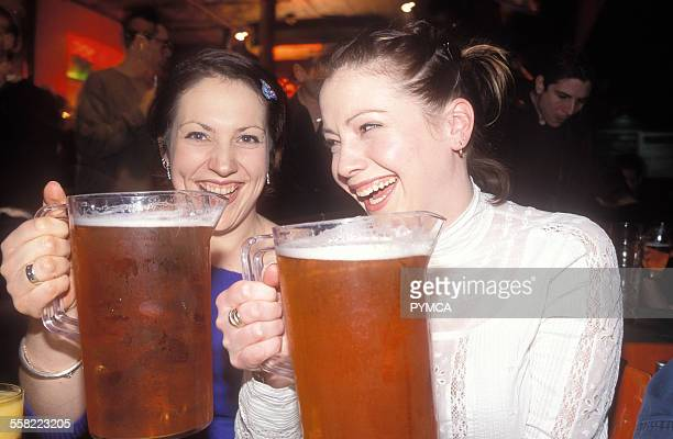 Two women laughing with big pints of beer UK 2004