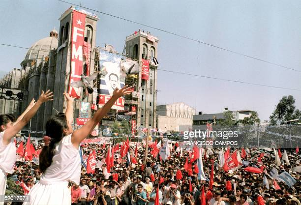 Two women launch doves 16 January 1993 in the central plaza of the Salvadoran capital where thousands of Salvadorans have gathered to celebrate the...