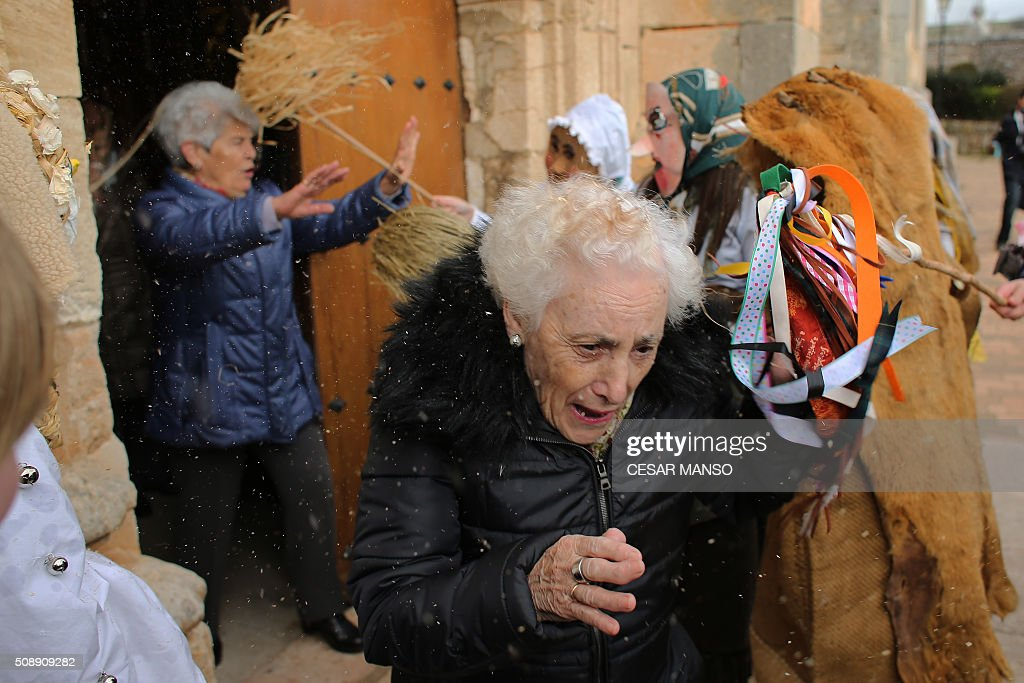 Two women leave the church as participants throw feathers and resin during the celebration of 'El Gallo de Carnaval' (The Carnival's Cock) in Mecerreyes, in the northern Spanish province of Burgos, on February 7, 2016. The Gallo Carnival is a pagan festival in which people participate singing, dancing and attacking the 'Gallo' that is defended by Zarramacos. AFP PHOTO / CESAR MANSO / AFP / CESAR MANSO