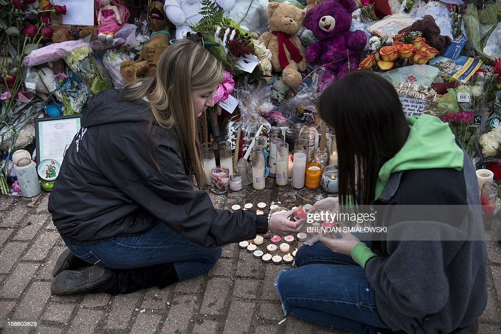 Two women light candles at a makeshift memorial on December 20, 2012 in Newtown, Connecticut. People continue to mourn the killing of 20 students and 6 adults by gunman Adam Lanza at Sandy Hook Elementary School last December 14. AFP PHOTO/Brendan SMIALOWSKI