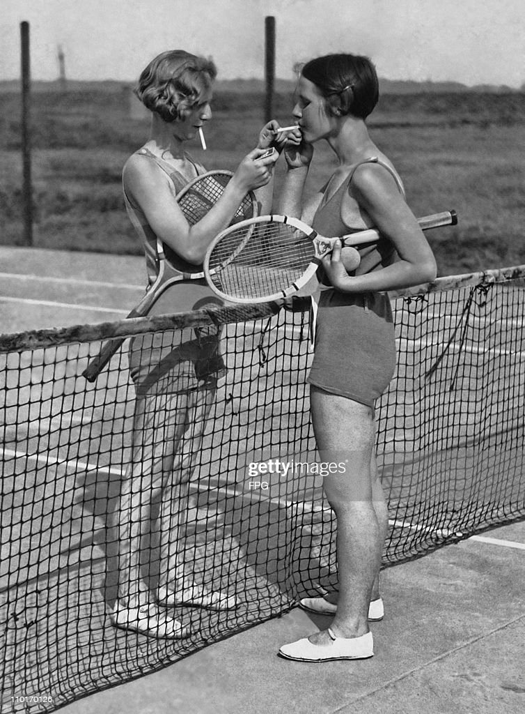 Two women lighting cigarettes on a tennis court in Essex, England circa 1930's.