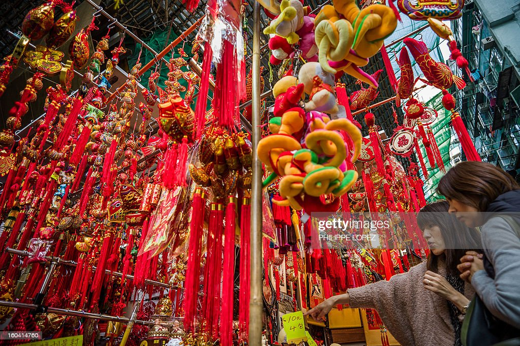 Two women look at a display of Chinese New Year items for sale at a street market in Hong Kong on January 31, 2013. The Chinese New Year of the snake falls on February 10, 2013. AFP PHOTO / Philippe Lopez