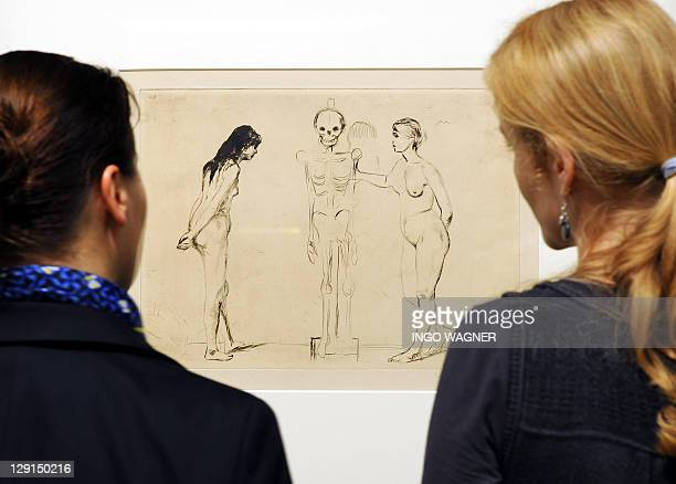 Two women look at a picture 'Die Frauen und das Gerippe 1896' by Norwegian artist Edvard Munch on display at the 'Kunsthalle Bremen' gallery in the...