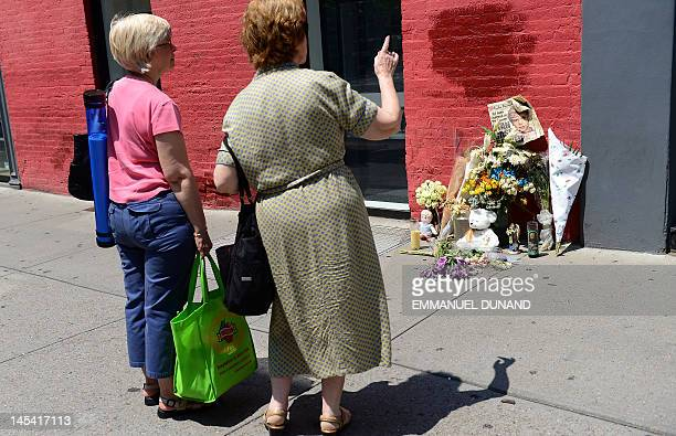 Two women look at a street shrine to sixyearold Etan Patz who disappeared 33 years ago set in front of the building where suspect Pedro Hernandez...