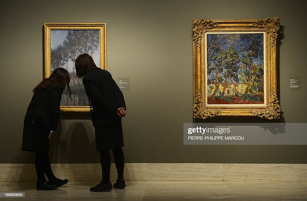 Two women look at a work by Claude Monet entitled 'Poplars on the bank of the Epte, sunset' at the Thyssen Bornemisza museum in Madrid on February 4, 2013, during the exhibition 'Impressionism and Open-air Painting. From Corot to Van Gogh'. AFP PHOTO / PIERRE-PHILIPPE MARCOU