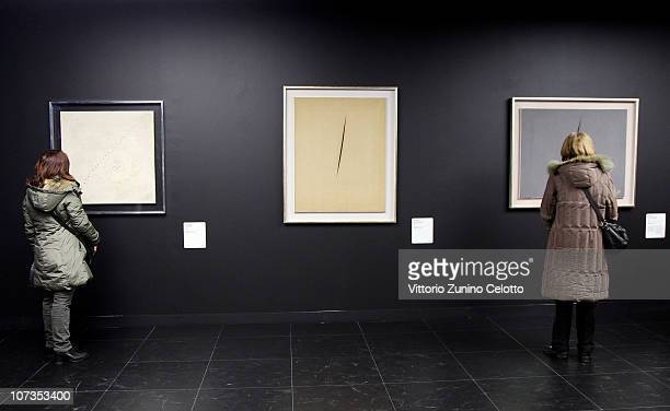 Two women look at 'Concetto Spaziale Attesa' by Lucio Fontana during the Museo Del Novecento Opening on December 6 2010 in Milan Italy