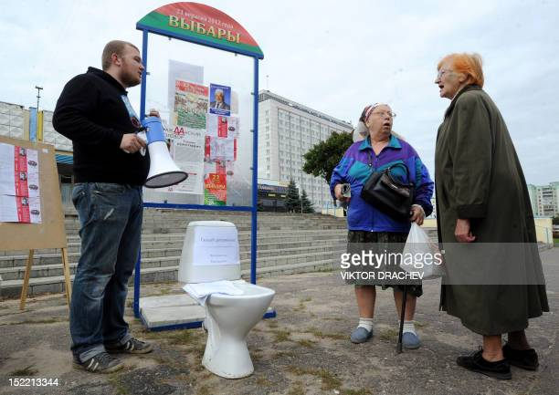 Two women look at election posters in Minsk on September 17 2012 as a man with a megaphone stands beside a toilet bowl The two of the biggest...