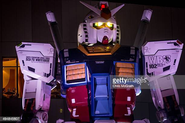 Two women look out from a restaurant window at Gundam an 18meter tall giant robot on permanent display at Odaiba on May 31 2014 in Tokyo Japan Odaiba...