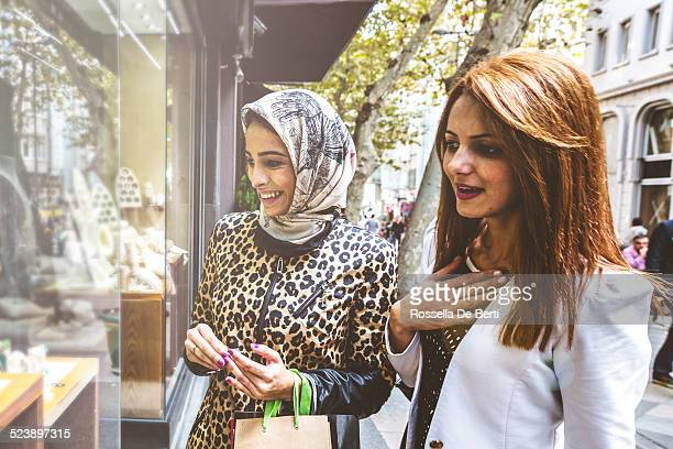 Two women looking at a jewelry store window.