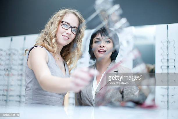 Two women looking at eyeglasses in opticians shop