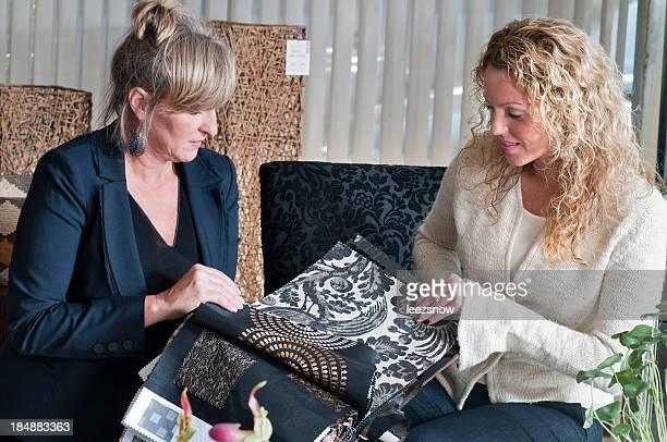 Two Women Looking At Fabric Swatches