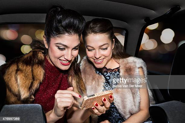 Two women looking at phone in car at night.