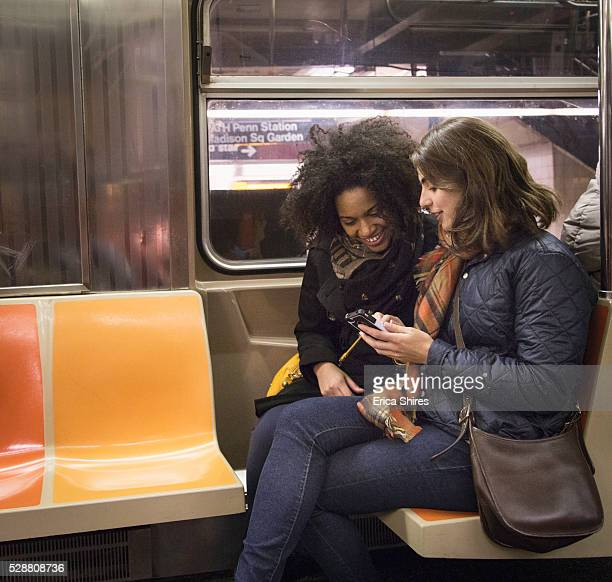 Two women looking at phone in train