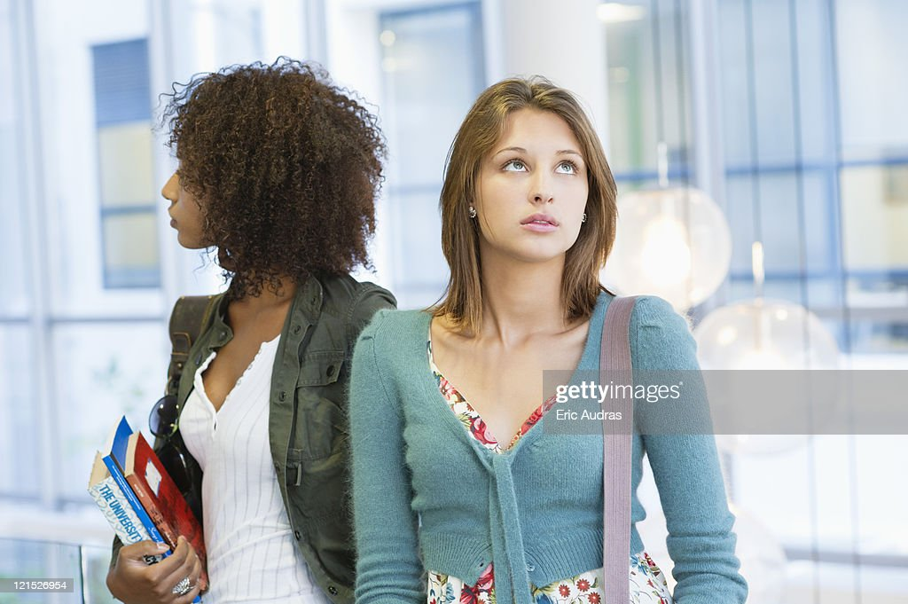 Two women looking away with books in hand at university : Stock Photo