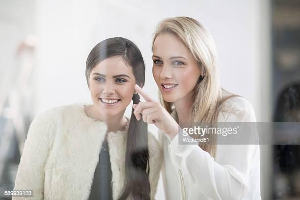 Two women looking through store window