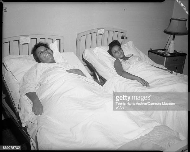 Two women lying in hospital beds including one on right wearing light colored dot patterned sleeveless nightgown with dark bows at straps resting in...