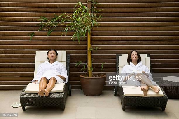 Two women lying in lounge chairs