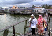 Two women make their way home through Kampong Ayer water village at dusk as the Sultan Omar 'Ali Saifuddien mosque is illuminated in the city of...