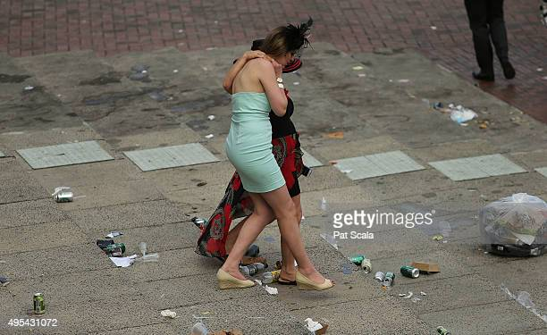Two women make their way through discarded beer cans as they attend the 2015 Melbourne Cup Day at Flemington Racecourse on November 3 2015 in...