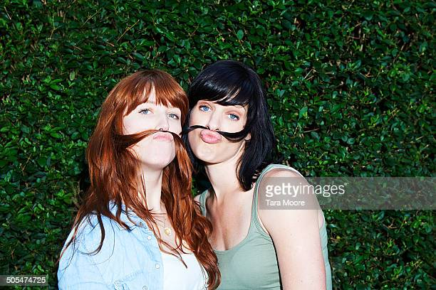 two women making moustaches with hair