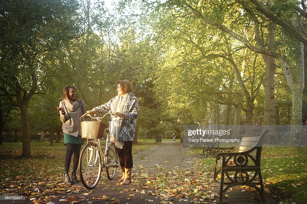 Two women meet & chat together in a London park : Stock Photo