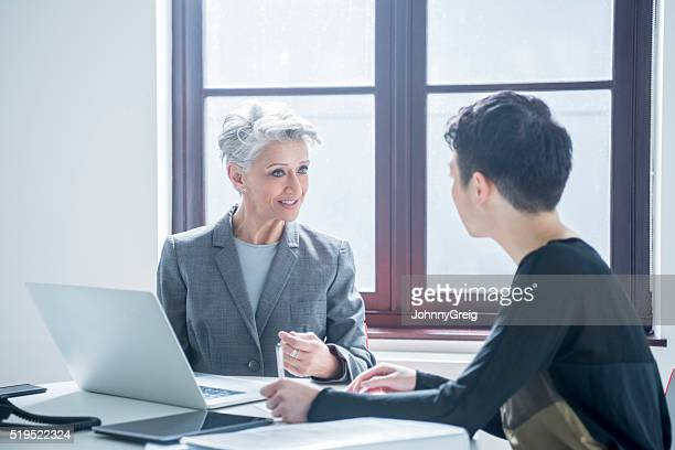 Two women meeting in modern office with laptop