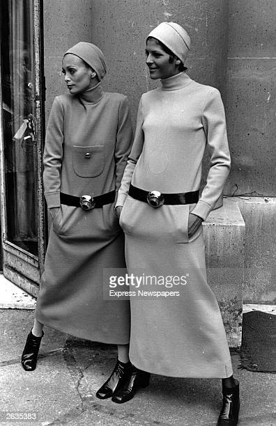 Two women model the Pierre Cardin fashions to be presented at the French Fashion Collection in April 1969 A long dress long sleeves high neck and no...