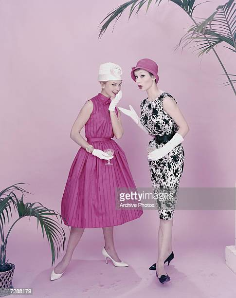 Two women modelling women's fashions in a studio portrait both stand holding wine glasses with one wearing a pink sleeveless dress with a white hat...