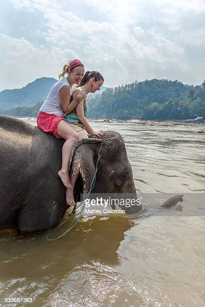 Two women on a elephant bathing in the Mekong