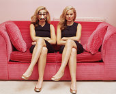 Two women on a sofa one wearing a comedy disguise