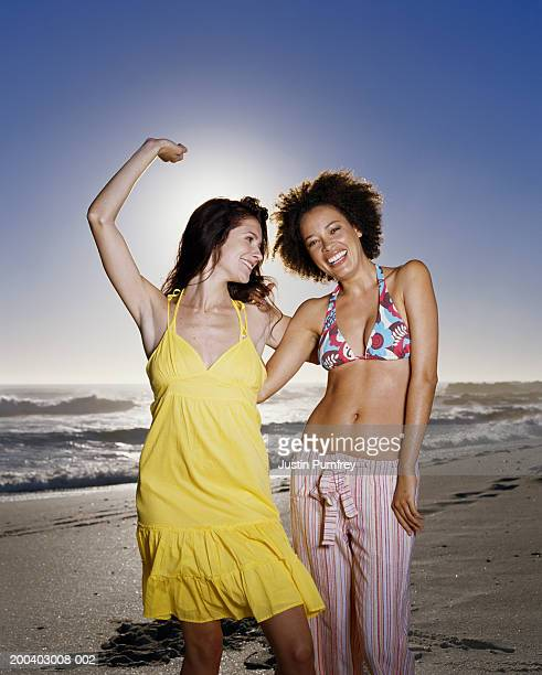 Two women on beach at sunset, one with arm raised, smiling, portrait