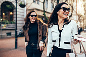 Two women on city street having fun. Female friends on walking down the road and smiling outdoors.